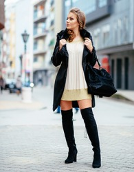 The model wore long boots to go with her short sweater dress.