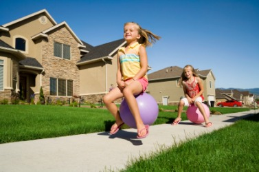 Two girls playing on bouncing balls.