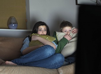 Cassie and her brother shudder in fear as they watch the horror movie on TV.