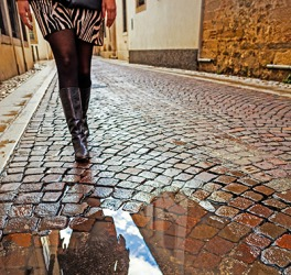 The woman will have to sidestep to avoid the puddle in the street.