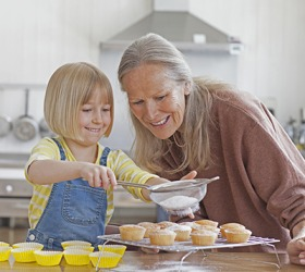 Emily's grandmother showed her how to use a sieve to sprinkle powdered sugar on the cupcakes.