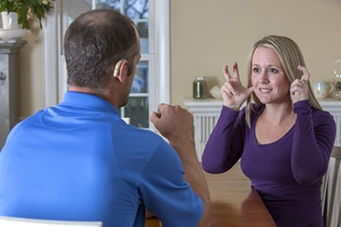 The deaf couple communicate using sign language.