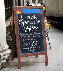 The restaurant signage advertising the lunch specials attracts people strolling down the sidewalk.