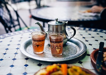 The Moroccan pomegranate tea is served on a silver-plate platter.
