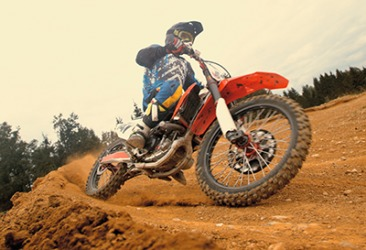 The dirt biker skid as he rounded the sharp turn of the course.
