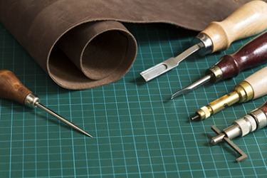 The tool in the top right corner is called a skiver and is used to skive leather.