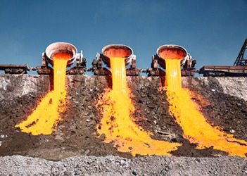 Molten slag is poured out of containers.