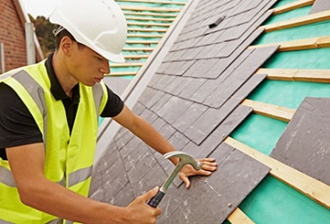 A construction worker is installing slate tiles on a roof.