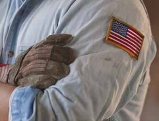 The worker has a patch of the American flag sewn on the sleeve of his shirt.