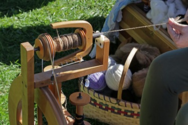 The woman slubs the lamb wool with the aid of a spinning wheel.
