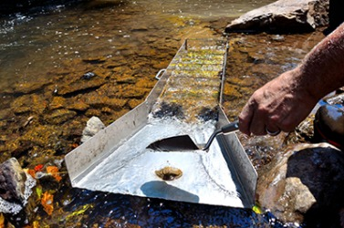 The prospector is panning for gold with a sluice box.