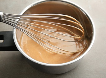 Gravy is thickened by whisking a cornstarch and water slurry into the boiling broth.