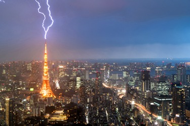 The lightening bolt smite the Tokyo tower during the thunderstorm.