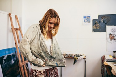 Marisa puts on her favorite smock when she works on her paintings.