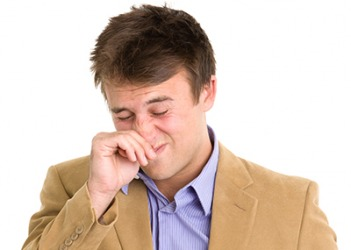 Andrew rubs his itchy nose and snorts due to sinus drainage from his seasonal allergies.
