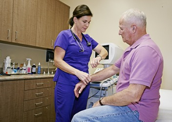 The nurse looks at the second hand on her watch while taking the patient's pulse.