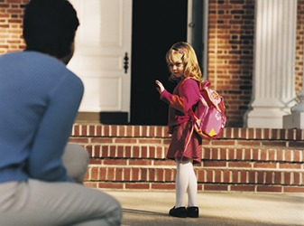 The anxious child waved goodbye to her mother on her first day of kindergarten.