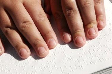 A person reading a book written in Braille.