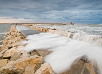 Waves crashing against a breakwater to a seaport.
