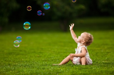 A baby playing with bubbles.