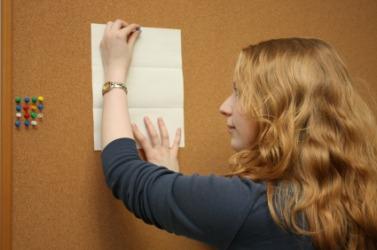A woman posting a bulletin on a bulletin board.