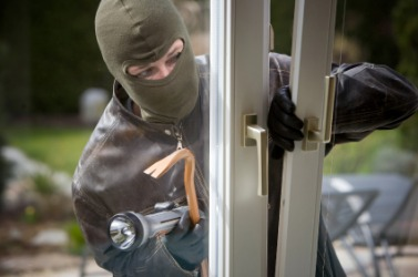 A burglar breaking into a house.