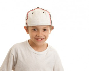 A young boy wearing a baseball cap.