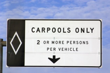 A sign designating the highway lane for carpools.