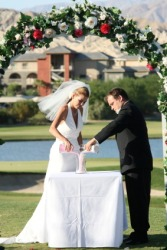 A couple participating in the sand ceremony at their wedding.