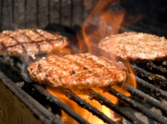 Hamburgers being charbroiled on a grill.