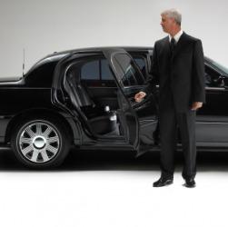 A chauffeur opening a car door.