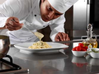 A chef putting the finishing touches on a plate of pasta.