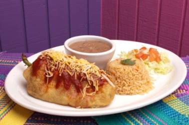 A dish of chile relleno with rice and beans.