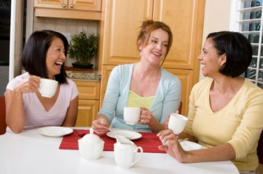 Three women enjoying a good chin-wag over a cup of coffee.