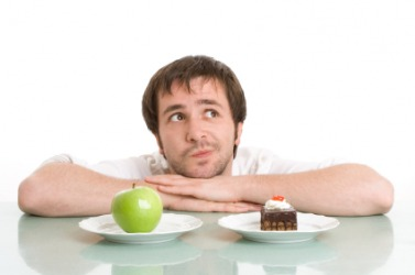 A man trying to make the choice between an apple or a dessert.