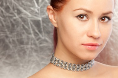 A woman wearing a pearl choker.