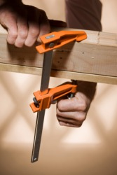 Two boards being held together by wood clamps.