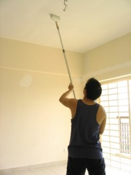 A man painting a ceiling.