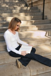 A coed studies on the college steps.