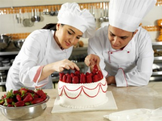Two chefs working to decorate a cake.