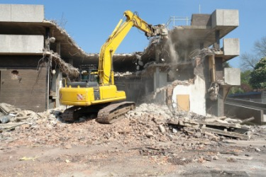 An excavator engaged in the destruction of a building.