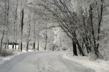 It would be very cold walking down this snowy road.