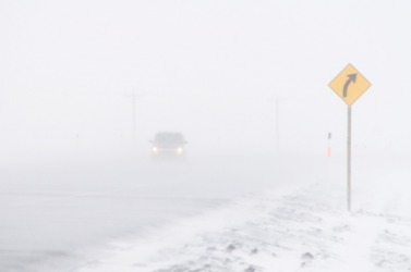 A car driving down the road is nearly hidden by the blizzard.