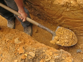 A man using a spade to dig a trench.