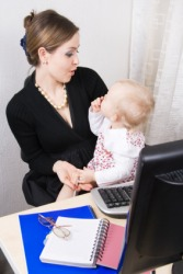 A baby distracts her mother from her work.