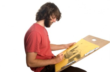 An artist using a drawing board.