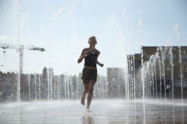 A girl getting drenched running through a fountain.