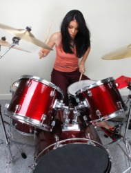 A woman playing the drums.