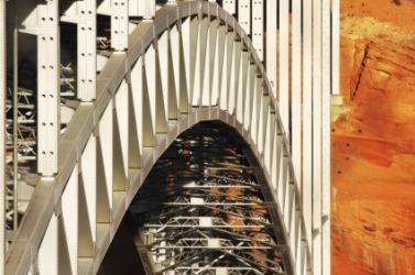 The girders of a suspension bridge form an arc.