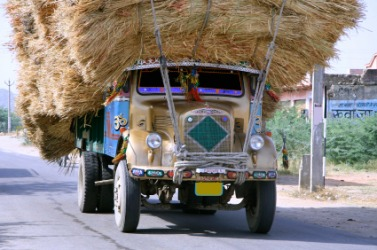 A truck with an encumbrance of hay.